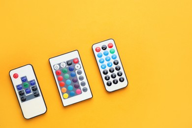 Remote controls on yellow background, flat lay. Space for text
