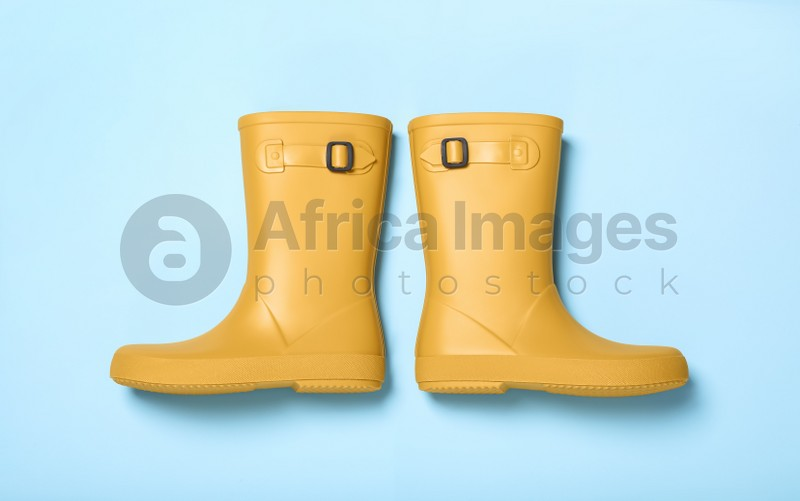 Pair of yellow rubber boots on light blue background, top view