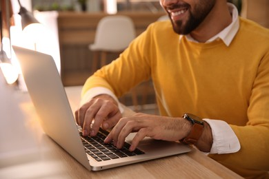 Man working with laptop at table in cafe, closeup