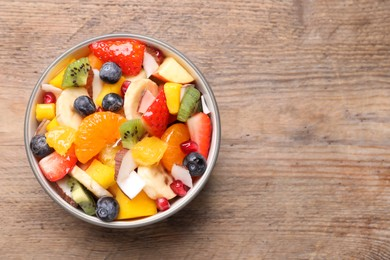 Delicious fresh fruit salad in bowl on wooden table, top view. Space for text
