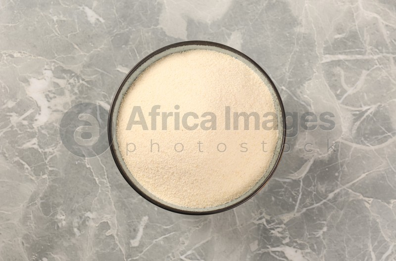 Uncooked organic semolina in bowl on grey table, top view