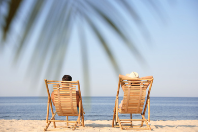 Couple resting on sunny beach at resort