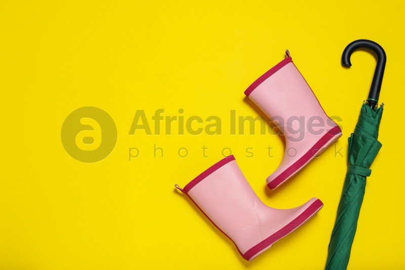 Pair of pink rubber boots near green umbrella on yellow background, flat lay. Space for text