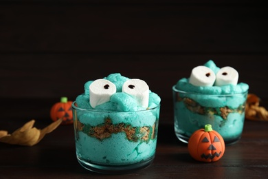 Delicious desserts decorated as monsters on wooden table. Halloween treat