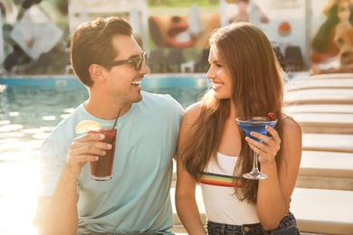 Happy young couple with fresh summer cocktails relaxing near swimming pool