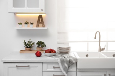 Modern kitchen interior with bowl full of ripe apples on counter