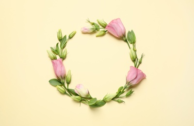 Frame of beautiful Eustoma flowers on beige background, flat lay. Space for text
