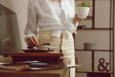 Woman using turntable at home, closeup view