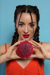 Young woman with fresh pitahaya on light blue background. Exotic fruit