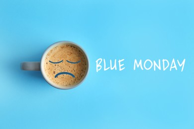 Cup of coffee and text Blue Monday on turquoise background, top view