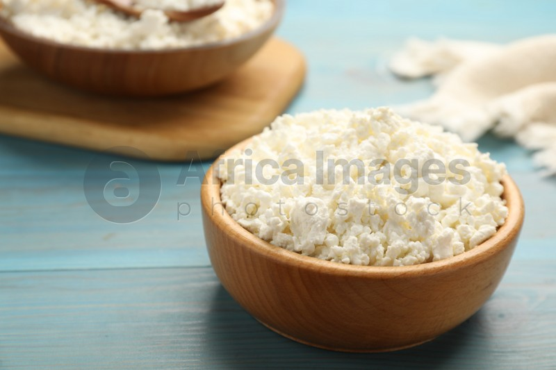 Delicious fresh cottage cheese on blue wooden table, closeup. Space for text