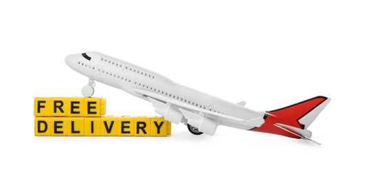 Toy plane and cubes with words FREE DELIVERY isolated on white. Logistics and wholesale concept