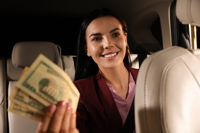 Young woman with money in modern taxi