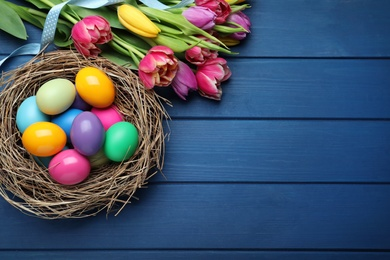 Bright painted eggs and spring tulips on blue wooden table, flat lay with space for text. Happy Easter