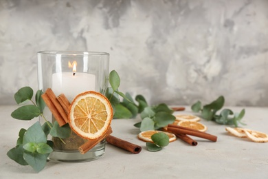 Stylish holder with burning candle and decor on light stone table. Space for text