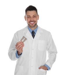 Professional pharmacist with pills on white background