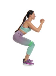 Woman doing squats with fitness elastic band on white background