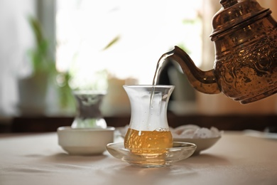Pouring hot tea into glass cup on table