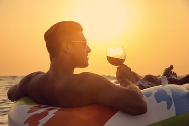 Man with glass of wine and inflatable ring in sea at sunset