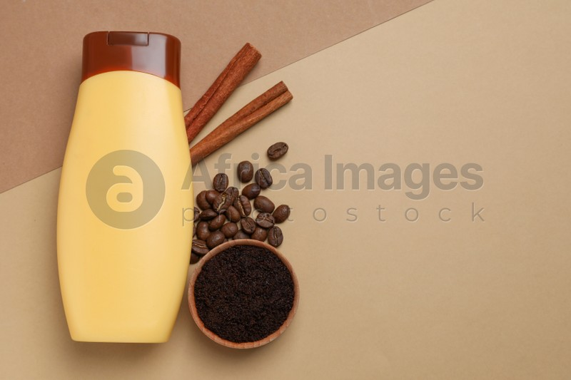 Bottle of shower gel, cinnamon, coffee beans and scrub on color background, flat lay. Space for text