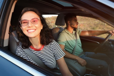 Happy young couple traveling by family car on summer day