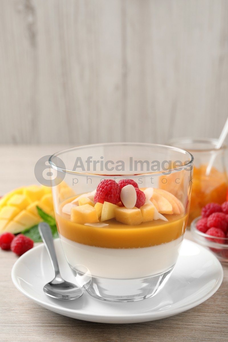 Delicious panna cotta with mango coulis, fresh fruit pieces and almond flakes on light wooden table
