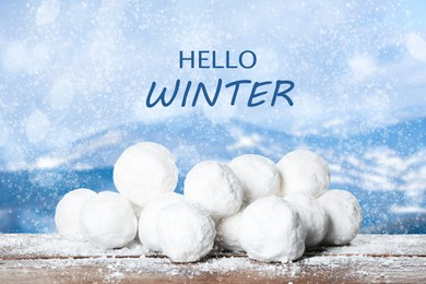 Hello Winter. Snowballs on wooden surface and blurred view of mountains