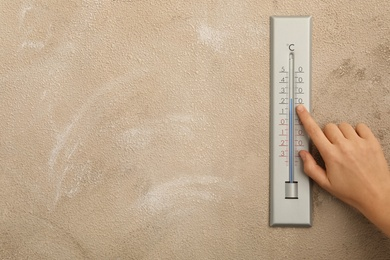 Woman with weather thermometer on beige background, closeup. Space for text
