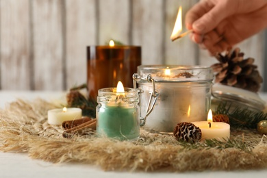 Woman lighting conifer candles on table, closeup