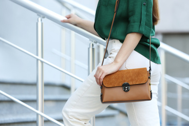 Young woman with stylish leather bag outdoors on summer day, closeup