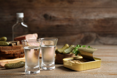 Cold Russian vodka with snacks on wooden table