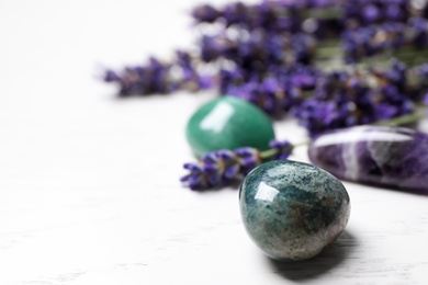 Gemstones and healing herbs on white wooden table, closeup. Space for text
