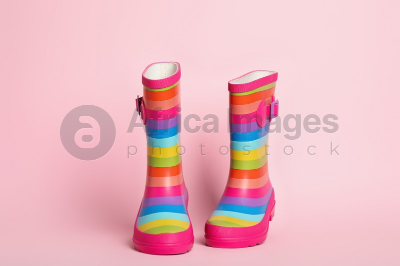 Pair of striped rubber boots on pink background