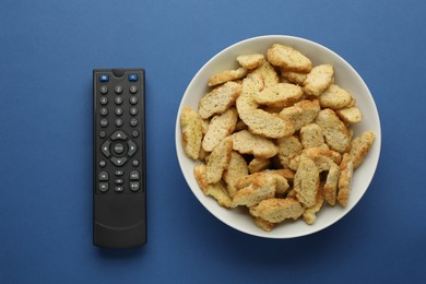 Remote control and rusks on blue background, flat lay