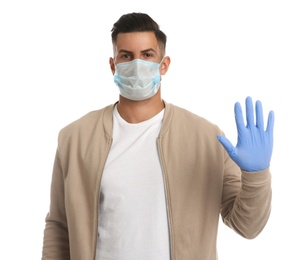Man in protective face mask and medical gloves showing stop gesture on white background