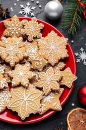 Tasty Christmas cookies, fir branches and festive decor on black table, flat lay