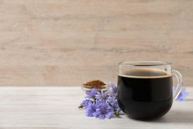 Glass cup of delicious chicory drink and flowers on white wooden table, space for text