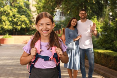 Parents waving goodbye to their daughter before school outdoors