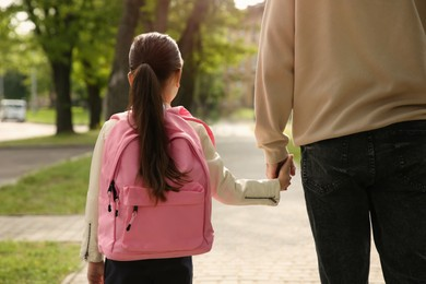 Father taking his little daughter to school through park, back view