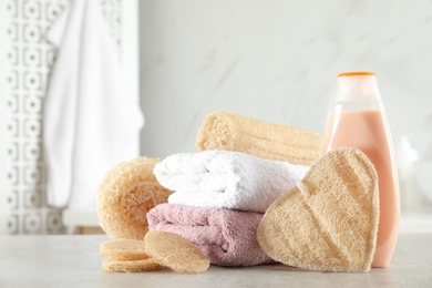 Natural loofah sponges, towels and bottle with cosmetic product on table in bathroom