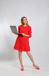 Full length portrait of young woman with modern laptop on light grey background