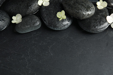 Stones and flowers in water on dark background, space for text. Zen lifestyle