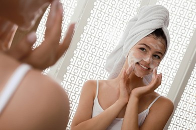 Beautiful teenage girl applying cleansing foam onto face near mirror at home. Skin care cosmetic