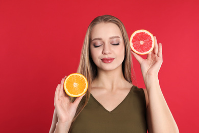 Young woman with cut orange and grapefruit on red background. Vitamin rich food