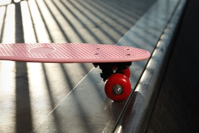 Modern pink skateboard with red wheels on top of ramp outdoors, closeup