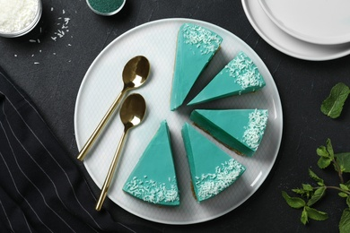 Flat lay composition with tasty spirulina cheesecake on dark table