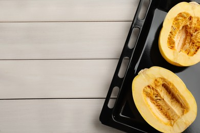 Halves of fresh spaghetti squash in baking sheet on white wooden table, top view with space for text. Cooking vegetarian dish
