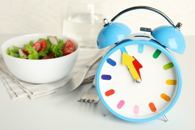 Alarm clock with salad on white table, closeup. Meal timing concept