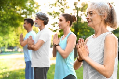 Group of people practicing morning yoga in park