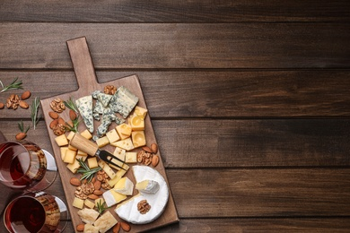 Cheese plate with rosemary and nuts on wooden table, flat lay. Space for text